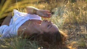 A menina moreno encaracolado na configuração branca da camisa na terra e fuma a junção no campo vídeos de arquivo