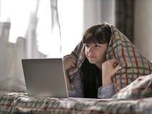 A menina moreno está encontrando-se sob as tampas e está olhando-se no portátil imagens de stock royalty free