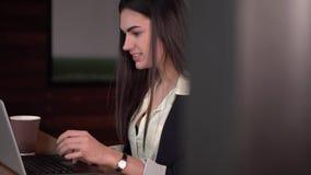 A menina moreno está falando em Skype que datilografa no portátil e no café bebendo vídeos de arquivo