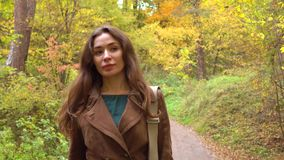Menina moreno feliz bonita que anda através das madeiras do outono closeup Foto de Stock Royalty Free