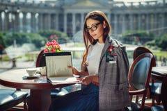 A menina moreno glamoroso e à moda bonita senta-se em um café e foto de stock