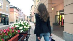 A menina moreno magro borrada nas calças de brim anda com seus purchasings nos sacos perto das lojas outlet vídeo do fundo do bok vídeos de arquivo