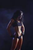 Menina moreno muscled nova 'sexy' da aptidão que levanta sobre o fundo preto Imagem de Stock Royalty Free