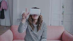 A menina moreno natural atrativa usa vidros de uma realidade virtual em casa Move suas mãos ao interagir com filme