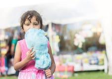 Menina moreno no algodão doce justo comer da cidade imagens de stock royalty free