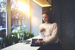 A menina moreno nos vidros executa os clientes diários do trabalho que notam as melhores ideias e solução no caderno pessoal Imagens de Stock
