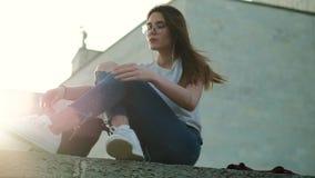 A menina moreno nos vidros senta-se no por do sol escuta a música amarra acima laços video estoque