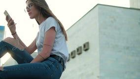 A menina moreno nos vidros senta-se no por do sol escuta a música e lê mensagens filme