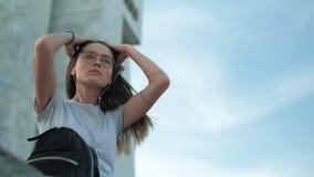 A menina moreno nos vidros senta-se no por do sol escuta a música que procura algo em um close-up da trouxa filme