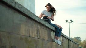 A menina moreno nos vidros senta-se no por do sol escuta a música que procura algo em uma trouxa vídeos de arquivo