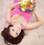 Menina moreno nova bonita que coloca na areia seaside Holid foto de stock