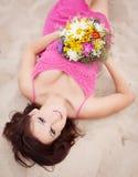 Menina moreno nova bonita que coloca na areia seaside Holid Imagens de Stock Royalty Free
