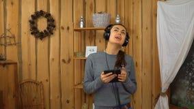 Menina moreno nova com música de escuta dos fones de ouvido da tabuleta filme