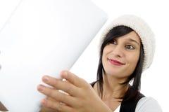 Menina moreno nova com a tabuleta isolada no fundo branco Foto de Stock
