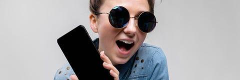 Menina moreno nova em vidros redondos Os cabelos são recolhidos em um bolo Menina com um telefone preto Imagens de Stock