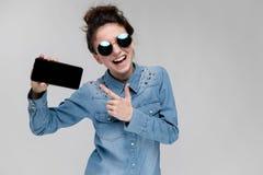 Menina moreno nova em vidros redondos Os cabelos são recolhidos em um bolo Menina com um telefone preto Imagens de Stock Royalty Free