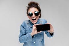 Menina moreno nova em vidros redondos Os cabelos são recolhidos em um bolo Menina com um telefone preto Fotografia de Stock
