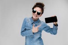 Menina moreno nova em vidros redondos Os cabelos são recolhidos em um bolo Menina com um telefone preto Foto de Stock