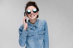 Menina moreno nova em vidros redondos Os cabelos são recolhidos em um bolo Menina com um telefone preto A menina está falando no Imagem de Stock