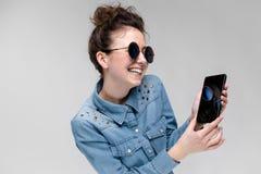 Menina moreno nova em vidros redondos Os cabelos são recolhidos em um bolo Menina com um telefone preto A menina está olhando Foto de Stock
