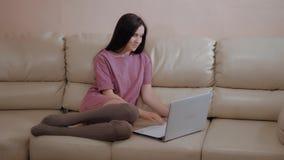 A menina moreno nova no meias mornas das peúgas, coloca no sofá de couro em casa e trabalhando no portátil filme