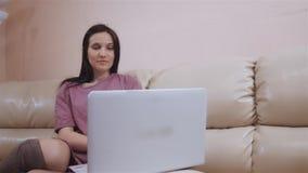 A menina moreno nova no meias mornas das peúgas, coloca no sofá de couro em casa e trabalhando no portátil vídeos de arquivo