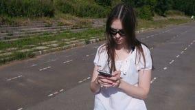 Menina moreno nova que anda no estádio e que datilografa uma mensagem em um telefone celular e em um sorriso filme