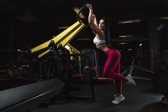 A menina moreno nova 'sexy' está fazendo para trás exercícios em instrumentos de formação no gym imagens de stock royalty free