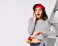 Menina moreno nova surpreendida com uma escova e uma escada - quanto trabalho a fazer imagem de stock