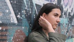 A menina moreno pensativa bonita nova está perto da parede com grafittis e corre sua mão através de seu cabelo filme
