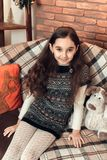 Menina moreno pequena agradável com o cabelo longo que senta-se em um sofá no ch Imagens de Stock Royalty Free