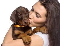 Menina moreno que beija seu cachorrinho isolado no fundo branco Fotografia de Stock Royalty Free
