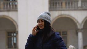 Menina moreno que fala no telefone que está no quadrado vídeos de arquivo