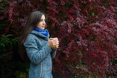 Menina moreno que guarda o copo amarelo do chá quente Foto de Stock