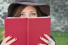 Menina moreno que guarda um livro vermelho Imagens de Stock Royalty Free