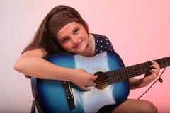 Menina moreno que joga a guitarra azul Fotos de Stock