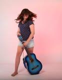 Menina moreno que joga a guitarra azul Fotos de Stock Royalty Free