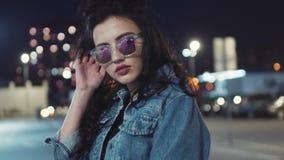 A menina moreno quente nova atrativa no revestimento das calças de brim e em óculos de sol à moda levanta pela câmera Olhar sedut filme