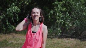 Menina moreno quente nova nos fones de ouvido que olham e que sorriem à câmera Mulher atrativa que ri e que dança no parque Bonit filme