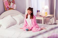 Menina moreno satisfeito que senta-se na cama em sua sala imagem de stock royalty free