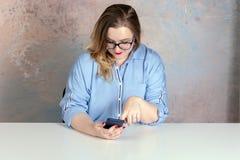 A menina moreno senta-se na tabela e nos olhares no telefone fotografia de stock