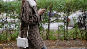 A menina moreno sozinha está andando na rua molhada do outono na cidade após a chuva no dia, datilografando em seu smartphone filme