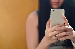 A menina moreno toma o selfie em um smartphone moderno do toque imagem de stock royalty free
