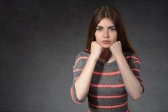 A menina mostra a concentração contra um fundo escuro Imagens de Stock Royalty Free