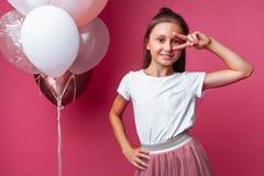 A menina mostra a mostras dois dedos, retrato da menina adolescente no fundo cor-de-rosa, com balões imagens de stock