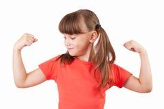 A menina mostra-nos seu bíceps imagens de stock