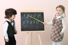 A menina mostra por figuras do ponteiro no quadro para o menino Fotografia de Stock