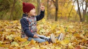 A menina mostra seu dedo no céu no parque no outono filme