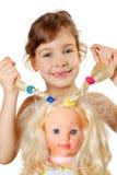 A menina mostra tranças das bonecas Imagem de Stock Royalty Free