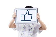 A menina mostra um polegar acima do ícone na tela da tabuleta Foto de Stock